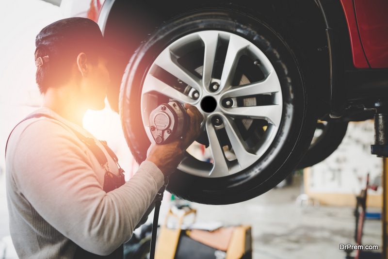 young mechanic working holding the device changing tyre of car