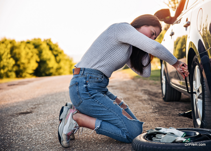 Woman changing wheel after a car breakdown